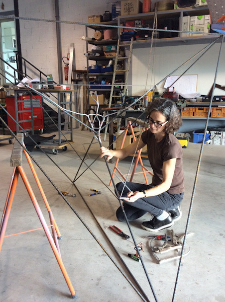 Photo of Briony attaching a human shaped aluminium armature to the steel tetrahedral armarture
